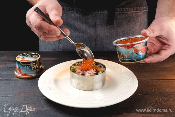Готовый тартар разложите на тарелки в виде небольших круглых башенок с помощью сервировочного кольца. Сверху каждой порции выложите слой красной икры «Восточный берег».