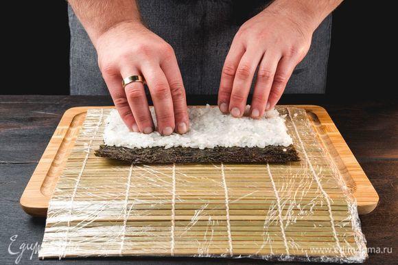 Лист нори выложите на циновку, накрытую пищевой пленкой. Смочите руки холодной водой и распределите рис на нори ровным слоем.