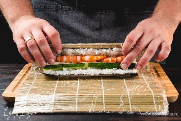 Сверху в ровную линию выложите креветки, мягкий сыр и нарезанный соломкой огурец. Скрутите ролл при помощи циновки, удалите пищевую пленку, разрежьте на несколько частей.