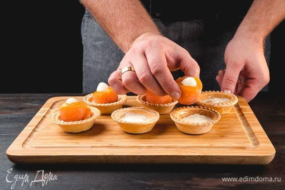 На тарталетку выложите сливочный сыр, в середину поставьте перепелиное яйцо, обернутое полоской лосося.