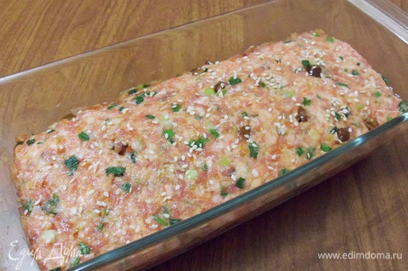 Сверху (по желанию) можно посыпать кунжутом. Поставить форму в разогретую до 200°C духовку на 1 час. Запеканка за это время должна уплотниться и отставать от краев формы.