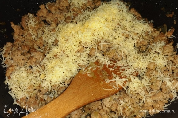 Добавить к обжаренному фаршу половину натертого сыра, перемешать.