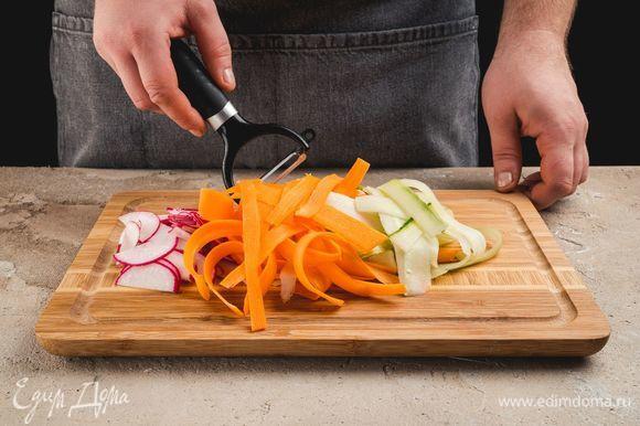 Морковь и огурцы очистите, нарежьте слайсами при помощи овощерезки. Редис нарежте тонкими полукольцами.