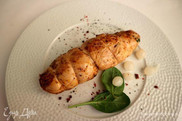 Снять кулинарную нить, на тарелку поместить несколько листиков шпината, молотый черный и розовый перцы, маленькие маринованные луковки.