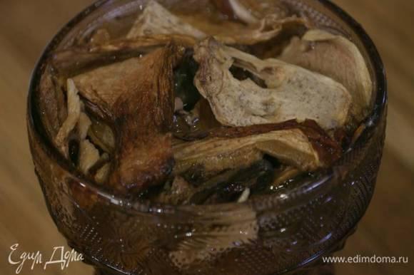 Грибы залить кипятком и дать постоять, затем жидкость слить и сохранить, а грибы мелко порезать.