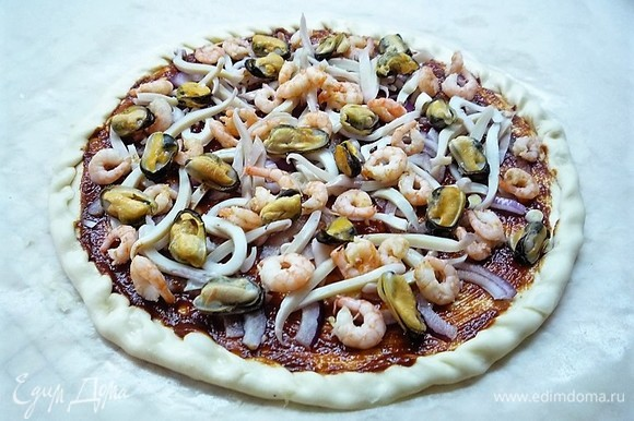 Поверх лука выкладываем нарезанного тонкими полосками кальмара, креветки и мидии. Посыпаем смесью итальянских трав и перцем.