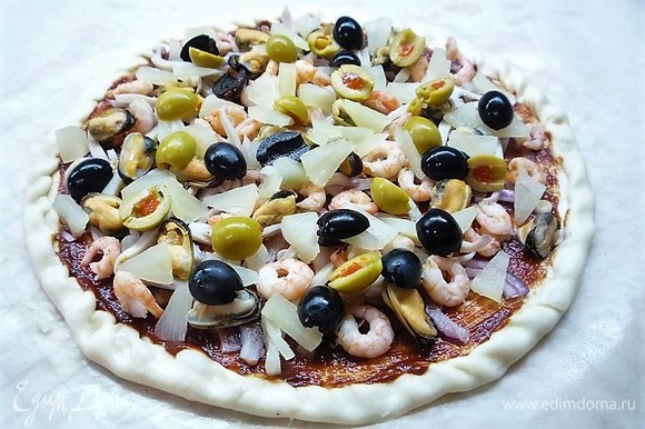 Поверх морепродуктов выкладываем мелконарезанные кусочки ананаса, нарезанные пополам оливки, маслины и каперсы.