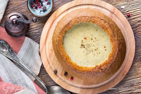 Постепенно ввести плавленый сыр в суп, варить еще пару минут, затем взбить блендером до однородности. Налить суп в горячий подрумяненный хлеб и приправить смесью перцев.