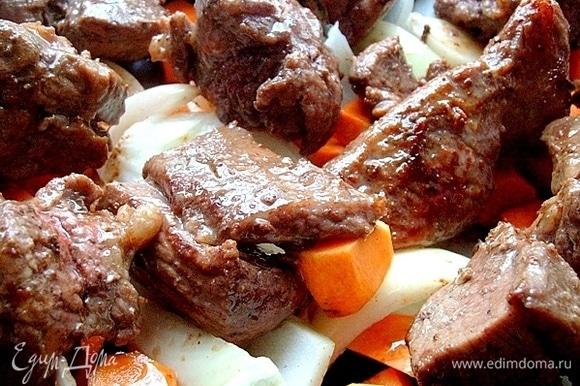 Смазываем маслом форму, в которой будем запекать мясо и овощи. Вниз кладем морковь, тыкву и лук, на них размещаем обжаренную телятину. Поливаем все соком, выделившимся при обжаривании. Отправляем мясо в горячую духовку на 30 минут. Выпекаем мясо при 170°C.