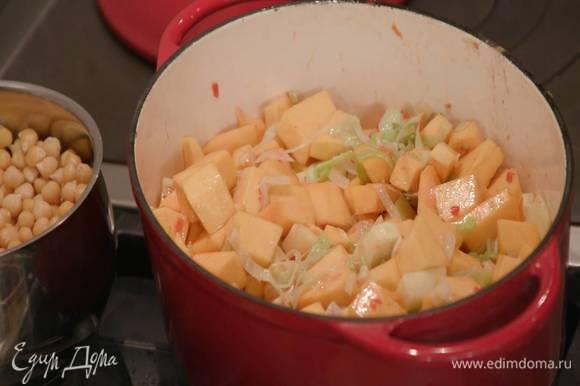 Тыкву и картофель почистить, нарезать небольшими кубиками, отправить в кастрюлю с луком и перемешать, затем добавить корицу, паприку, зиру, кориандр, мускатный орех, соус чили и еще раз перемешать.