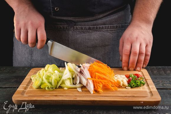 Нарежьте лук-порей, лук-шалот, сельдерей, морковь, перец чили и чеснок.