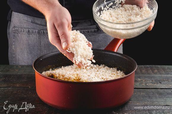 Добавьте рис. Варите 1,5 часа, не перемешивая, но периодически проводя лопаткой по стенкам сковороды, чтобы рис не пригорал.