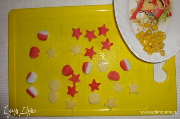 Из отложенных крабовых палочек и сыра вырезать кружки и звездочки.