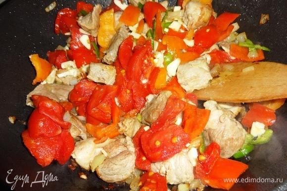 Помидоры и чеснок добавить в сковороду, перемешать.