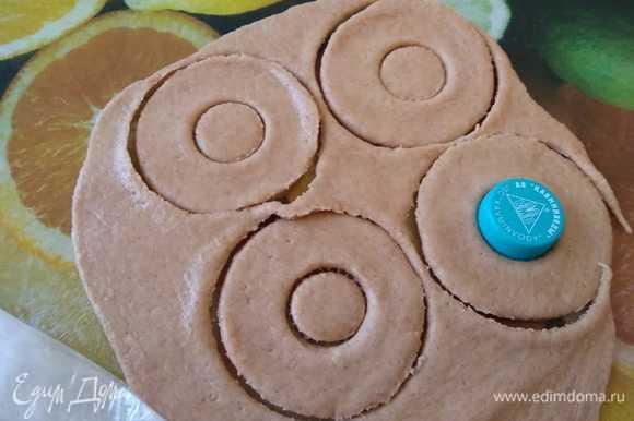 Тесто раскатать в пласт толщиной 0,5 см и широким стаканом вырезать кружки. Выемкой меньшего размера (у меня крышка от бутылки) из каждого кружка вынуть середину, придавая таким образом тесту форму пончика.