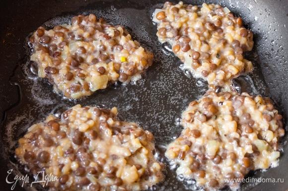 На разогретую сковороду с маслом выкладываем порционно столовой ложкой оладьи.