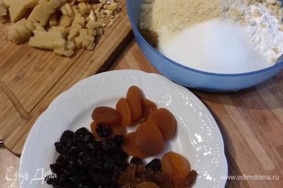В миске смешать муку, разрыхлитель, соль, сахар, молотый в мелкую крошку миндаль. Фисташки и миндаль крупно порубить и добавить к муке. Также порубить марципан, курагу, клюкву и изюм (если он крупный).