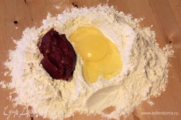 Начнем с красной пасты. Смешиваем оба вида муки, разбиваем туда яйцо и добавляем томатную пасту. Замешиваем тесто сначала вилочкой, потом — руками.