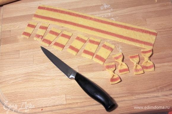 Затем нарезаем тесто на полоски шириной 3–4 см, а из полосок нарезаем прямоугольники размером примерно 4х2 см. Если есть дисковый нож с мелкими зубчиками, то можно делать заготовки с его помощью — получится красиво. Формируем из заготовок бантики.