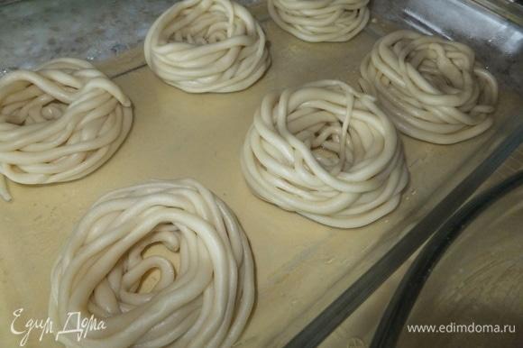 Смазываем форму сливочным маслом, кладем домашние спагетти в форму, сворачивая их в гнезда. Сюда же добавляем кусочки сливочного масла и 150 мл воды.