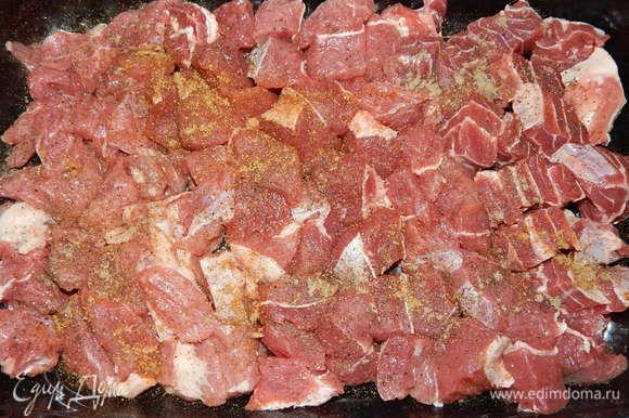 Мясо моем, режем средними кусочками. Форму для запекания смазываем подсолнечным маслом, выкладываем мясо, солим, перчим, добавляем хмели-сунели и приправу для мяса.
