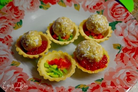 На дно тарталеток положить мелконарезанные лук и болгарский перец. Из подготовленной каши формируем шарики, выложить их поверх перчиков.