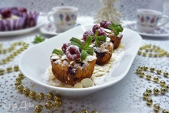 Даем маффинам немножко остыть, украшаем ягодками малины, листиками мяты. Посыпаем сверху сахарной пудрой и лепестками миндаля. Лепестки миндаля можно слегка обжарить на сухой сковороде.