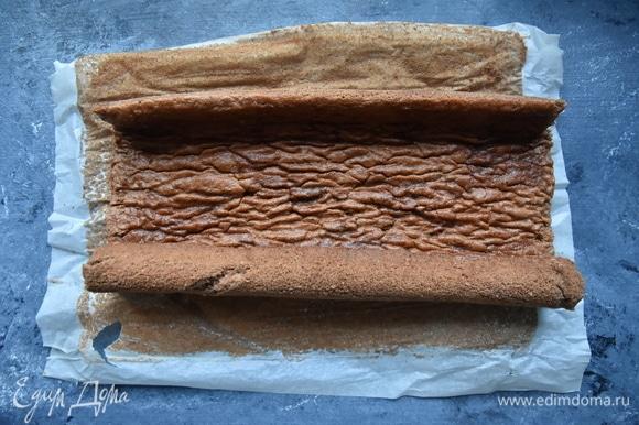Достать бисквит. Сверху на корж разложить чистое кухонное полотенце и вместе с бумагой и полотенцем свернуть бисквит в рулет. В таком виде дать ему полностью остыть.