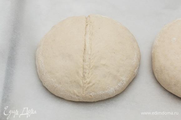 За полчаса до окончания расстойки включите духовку на 230°C, чтобы она как следует прогрелась. На дно духовки установите старую пустую сковородку, чтобы она прогрелась вместе с духовкой. После расстойки тесто увеличится в объеме и станет более мягким. Переложите его швом вниз на противень, застеленный бумагой для выпечки. Сделайте надрезы. Надрезы помогают тесту лучше и правильнее пропечься, поэтому надо наловчиться их правильно делать, я пока только учусь. Но могу сказать, что это лучше всего делать обычным бритвенным лезвием, держа его под углом примерно в 30°C к тесту. Глубина надреза, около 5–7 мм.