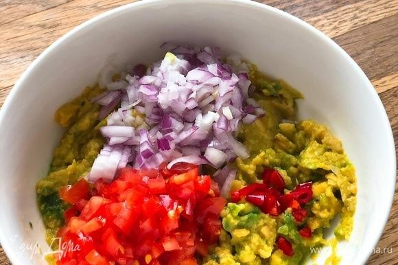 К пюре из авокадо добавить мелко нарезанный лук, помидор и перец чили.
