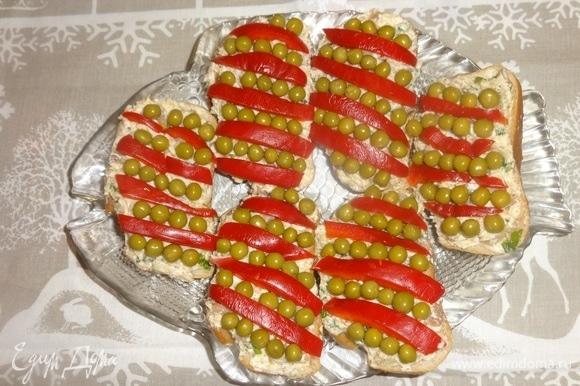 Украсить бутерброды полосками сладкого красного перца и зеленым горошком.