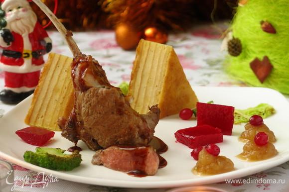 Осталось все выложить. Нарезаем пирог, выкладываем кусочки желе, капусту, клюкву, ставим каре, поливаем мясо соусом.