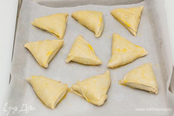 Подготовленные пирожки уложить на противень, смазать желтком и выпекать 20–25 минут при температуре 180°C.
