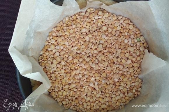 Наколоть тесто вилкой, сверху прикрыть бумагой для выпечки и насыпать фасоль или горох для груза. Выпекать 15 минут в разогретой до 180°C духовке. Убрать груз и допечь еще 5 минут.