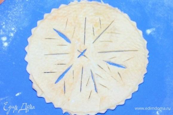 Раскатываем слоеное тесто на припыленной мукой доске и вырезаем 4 круга, диаметр которых должен быть на 2 см больше диаметра формочки. На круге можно вырезать снежинки.