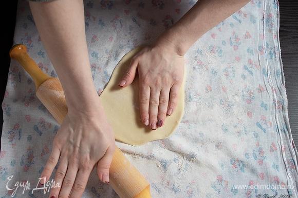 Начинается самый ответственный этап. На столе расстелите ткань, подпылите мукой. Выложите тесто на ткань и раскатайте скалкой как можно тоньше.