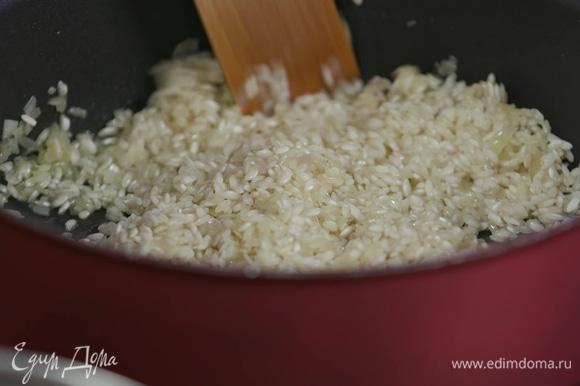 Добавить рис, перемешать, обжарить в течение минуты.