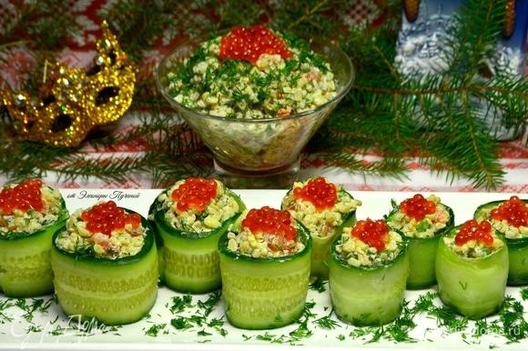 Огурец нарезаем тонкими длинными пластинами, кладем ложку подготовленной салатной смеси, сворачиваем в рулет, сверху украшаем икрой.