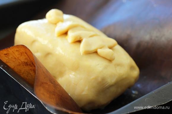 Переложить на раскатанное тесто. Свободные края смазать яйцом. Завернуть в конверт. Лишнее отрезать и хорошо защипнуть края. Переложить в форму, застеленную фольгой, швом вниз. Верх смазать желтком.