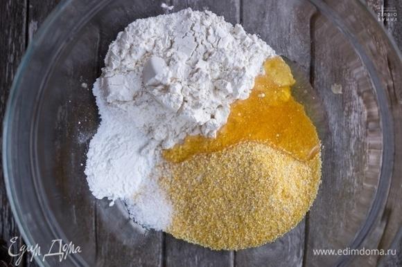 Пока свиные отбивные маринуются, приготовьте кукурузный хлеб. Поместите в миску кукурузную и пшеничную муку. Добавьте мед, разрыхлитель и соль. Перемешайте.