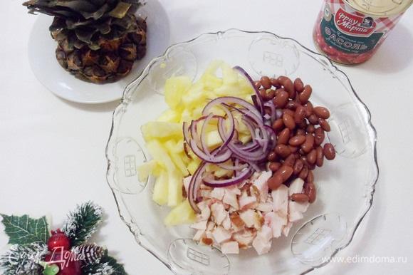 Нарезанную кусочками отварную грудку, ананас, красный лук и фасоль выложить в салатник.