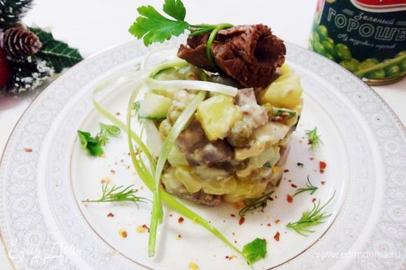 Можно украсить салат вьющимися нитями из перьев зеленого лука, а рулетик из ростбифа положить сверху.