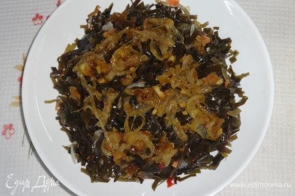 В салатник выложить морскую капусту. На нее выложить слой обжаренного лука.