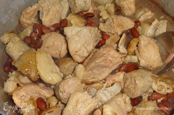 В кастрюлю с фасолью выложить обжаренные мясные продукты: свинину, бекон, колбаски. Продолжать тушить все вместе под закрытой крышкой. Если необходимо, долить немного воды.