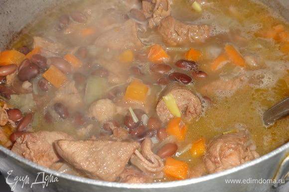 Когда свинина и фасоль станут достаточно мягкими, выложить в кастрюлю обжаренные лук с морковью.