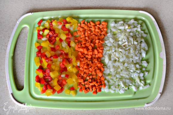 Перец, лук и морковь нарежьте небольшими кубиками. Затем пассеруйте около 3 минут на растительном масле вначале лук, затем добавьте морковь и еще через 3 минуты — перец. Слегка посолите и поперчите овощи.