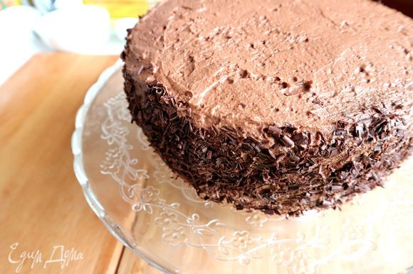 С помощью овощечистки приготовить шоколадную стружку для бортов. Обсыпать ею борта торта.