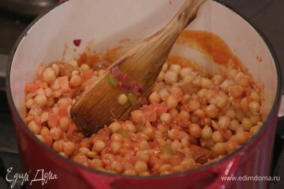 Добавить к овощам с колбасками томатную пассату и, помешивая, прогреть, затем всыпать отваренный нут и еще немного прогреть.