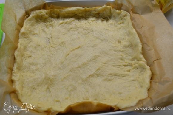 Форму диаметром 26 см выстелить бумагой для выпечки. Выложить тесто и разровнять по форме, формируя бортики.