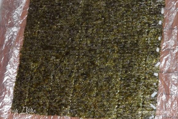 На циновке расстелить целофан. Положить лист нори. На один край нори выложить несколько рисинок для скрепления. На другом крае распределить слой крашеного риса .